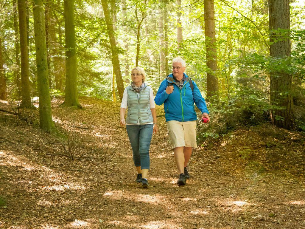 Ein Paar wandert durch den Neuenburger Urwald im strahlenden Sonnenschein