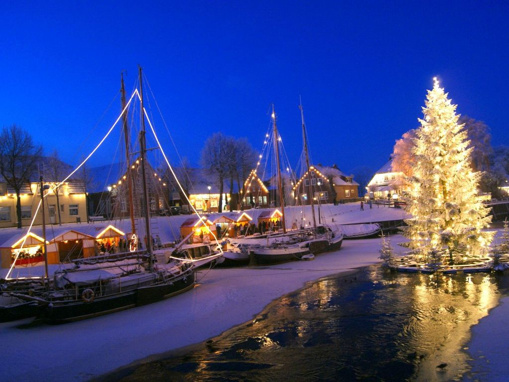 schwimmender Weihnachtsbaum im verschneiten Hafen