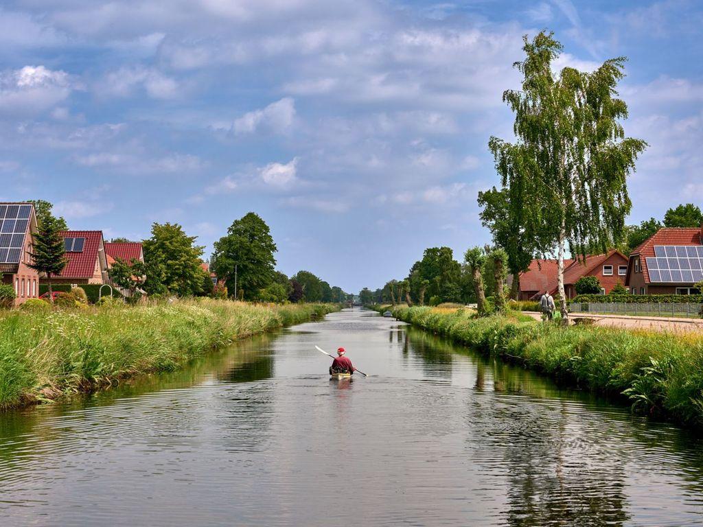 Dein Kanufahrer Paddelt auf einem Fehnkanal, an den Ufern stehen Wohnhäuser