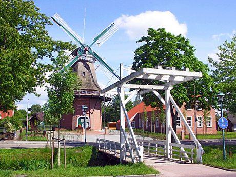 Weiße Klappbrücke im Sonnenschein vor der Mühle in Westrhauderfehn