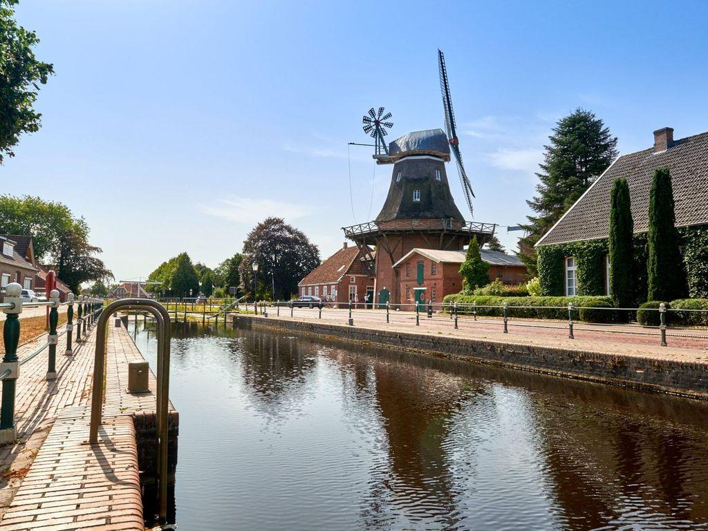 Sonnenschein über Kanal in Westgroßefehn mit Mühle im Hintergrund