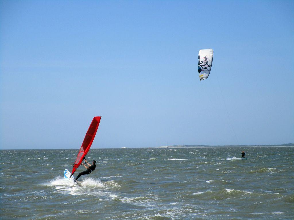Ein Kitesurfer und ein Windsurfer im Wasser vor Dornumersiel