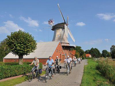 Eine Gruppe Fahrradfahrer vor der Mühle in Moormerland bei sommerlichem Wetter