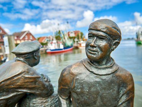 Bronzenes Denkmal von einem Alt- und Jungfischer im Hafen von Neuharlingersiel