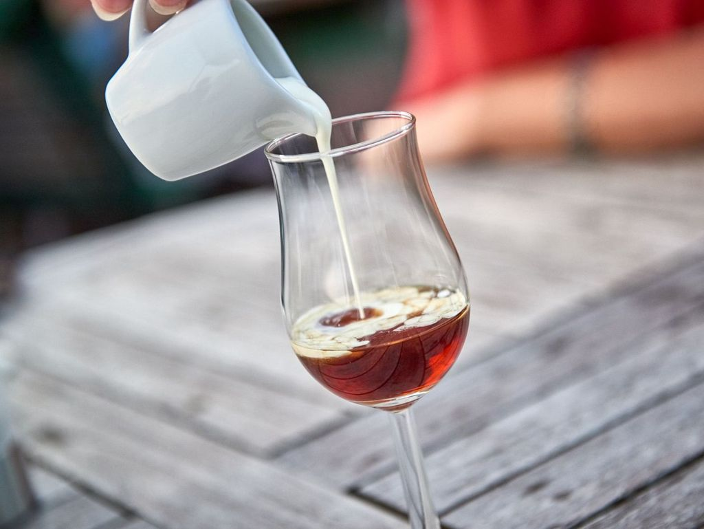 Sahne wird in ein Glas mit Teelikör gegossen