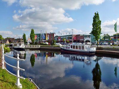 Kanal in Ostrhauderfehn mit einem Einkaufszentrum im Hintergrund