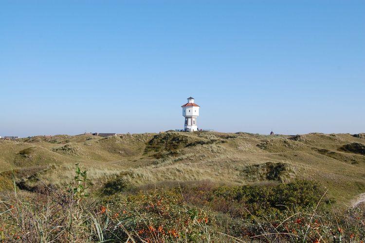 Blick über die Dünenlandschaft auf den Wasserturm von Langeoog