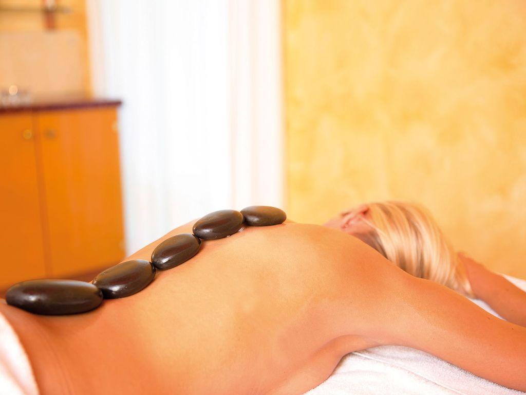 Eine Frau bei einer Hot Stone Massage mit Steinen auf dem Rücken
