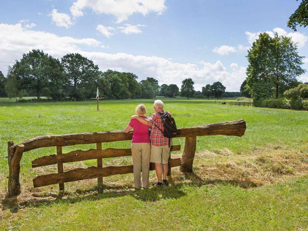 Ein Paar blickt bei einer Wanderung auf eine Scheuerpfahlskulptur auf einem Feld