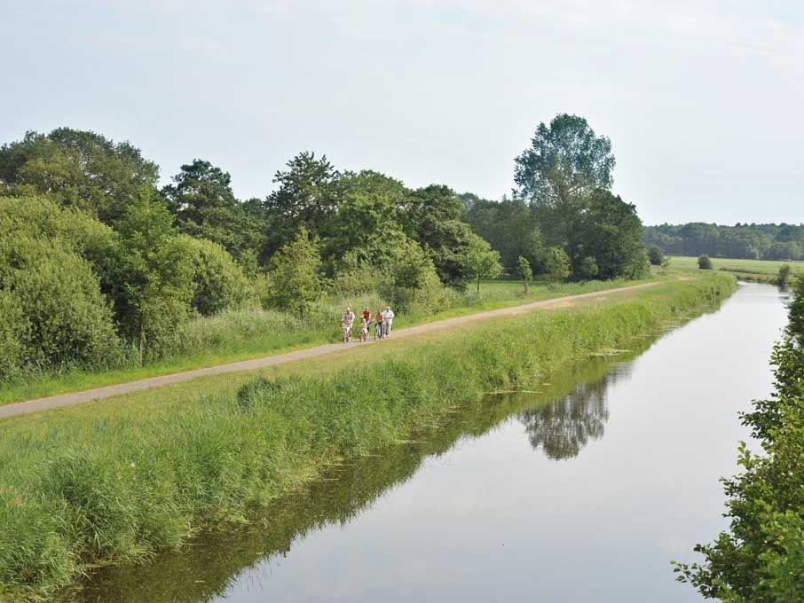 Eine Gruppe Fahrradfahrer auf einem Fahrradweg entlang eines Fehnkanals im Sommer