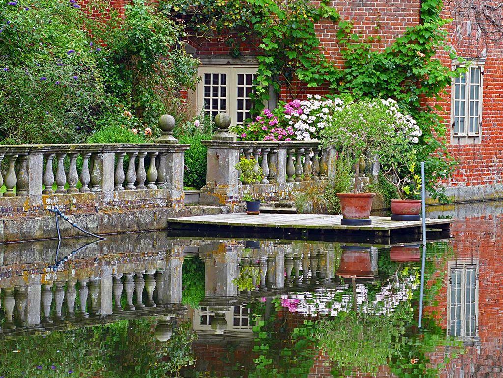 Steg und Hausfassade an einem Gewässer auf dem Gelände des Schloss Gödens