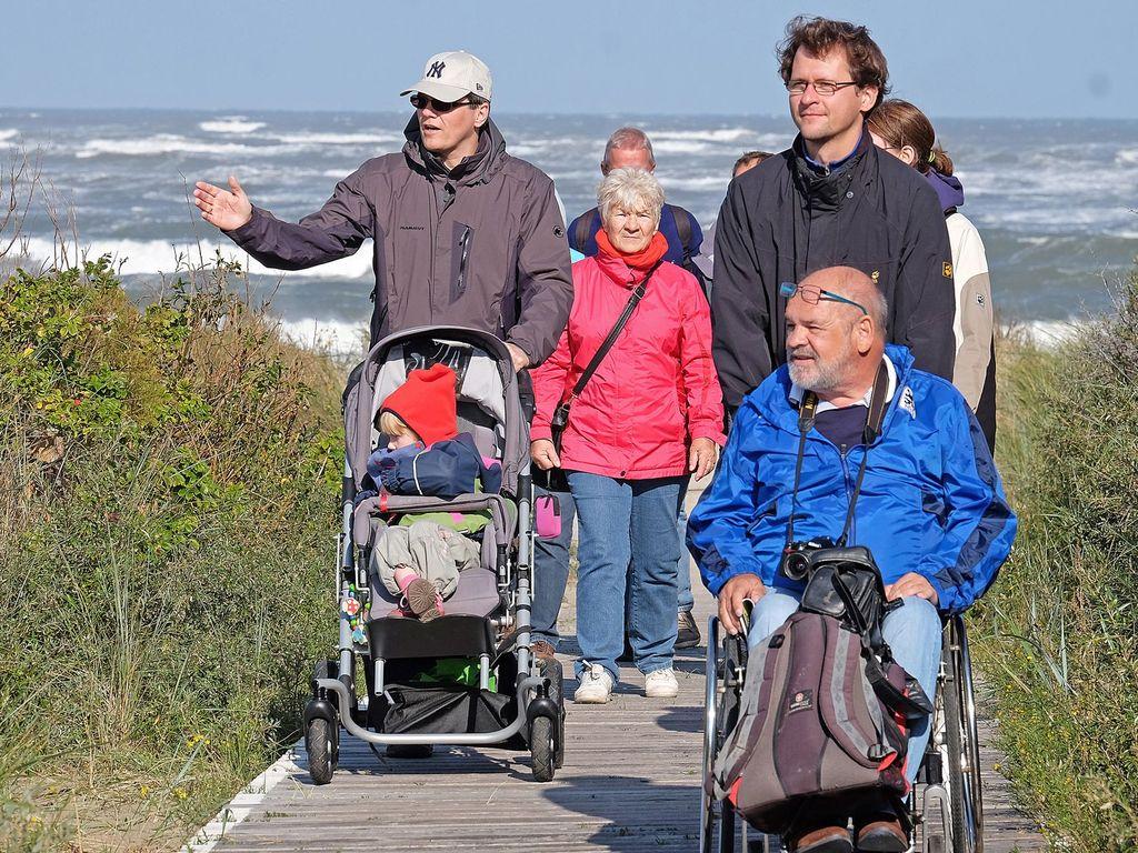 Menschen mit Kinderwagen und Rollstuhl auf dem barrierefreien Holzbohlenweg auf Langeoog