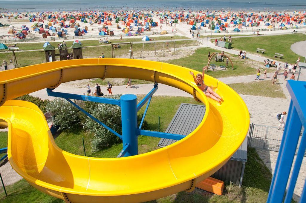 Gelbe Wasserrutsche mit Strand von Bensersiel im Hintergrund