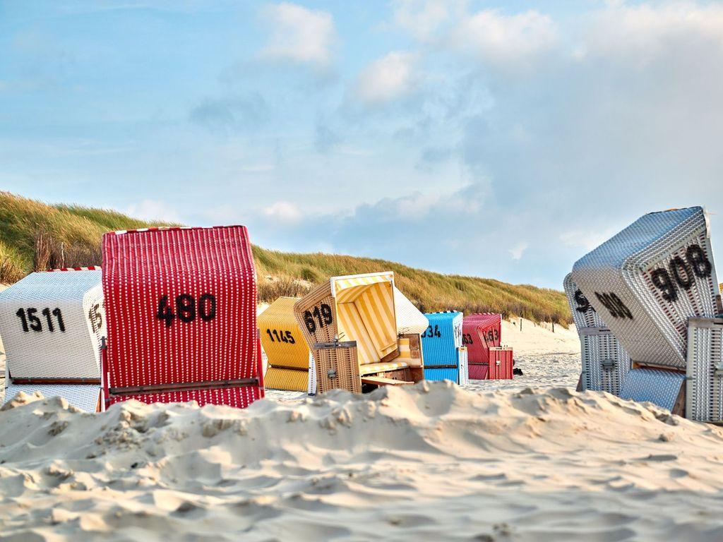 Bunte Strandkörbe im Sand auf Langeoog