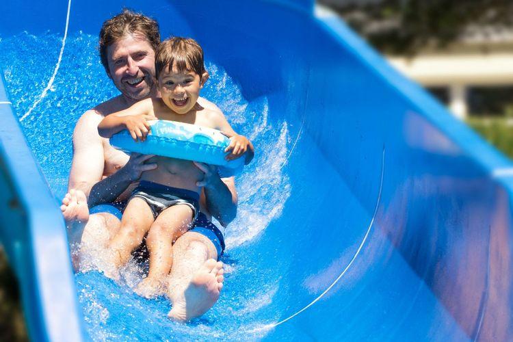 Ein Mann mit einem Kind auf einer Wasserrutsche
