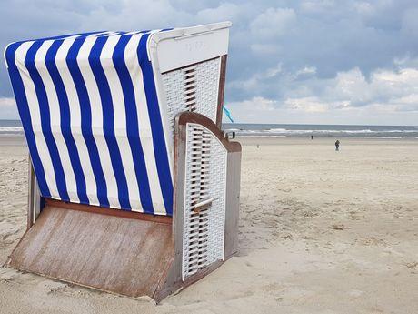 Detailblick auf einen blau-weiß-gestreiften Strandkorb im Sand an Strand von Norderney