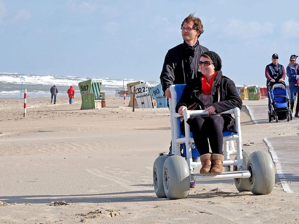 Eine Frau wird im Rollstuhl am Strand von Langeoog geschoben