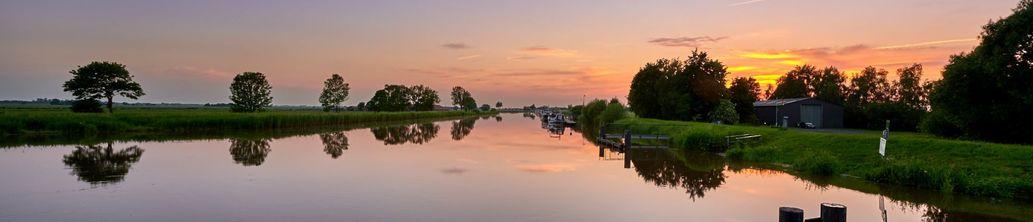 Sonnenuntergang über einem Kanal in Detern in Ostfriesland