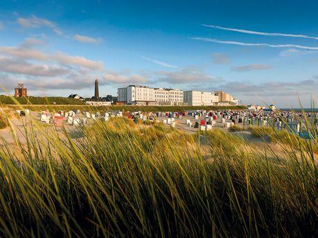 In den Borkumer Dünen mit Promenade und Strandkörben im Hintergrund