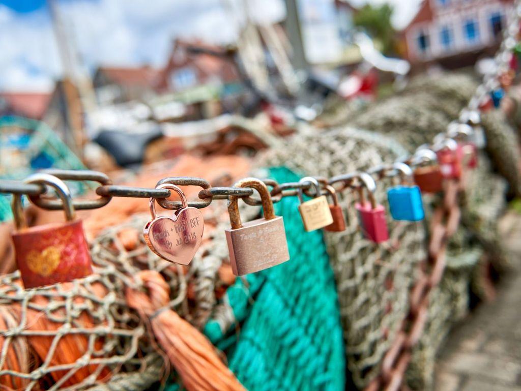 Bunte Liebesschlösser an einer Metallkette im Hafen von Neuharlingersiel