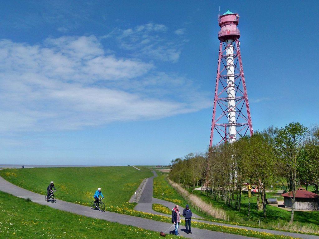 Fahrradfahrer und Fußgänger laufen auf dem Deichweg vor dem Campener Leuchtturm