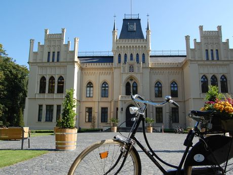 Außenansicht vom Schloss Evenburg bei blauem Himmel mit Fahrrad im Vordergrund