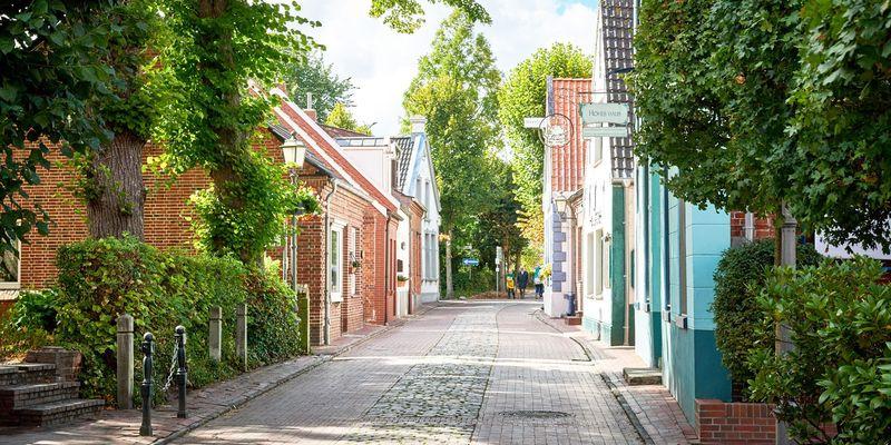 Eine schmale Straße in Greetsiel mit Häusern links und rechts
